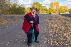 Senior hiker with walking stick sitting on an old green suitcase on the roadside Royalty Free Stock Photos