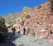 Senior hikers and Aztec sand stone rock formation. Image shows senior hikers walking past eroded sand stone rock formation in a desert wash near Red Rock Canyon Stock Photography