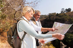 Senior hikers top mountain. Active senior hikers on top the mountain pointing at map royalty free stock image