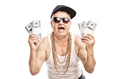 Senior in hip hop outfit holding a few stacks of money Stock Photos