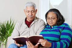 Senior Hipanic Couple Reading Bible Stock Photos