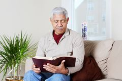 Senior Hipanic Man Reading Bible Stock Image
