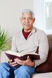 Senior Hipanic Man Reading Bible Stock Image