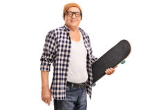 Senior hipster holding a skateboard. Studio shot of a senior hipster with a yellow hat holding a skateboard and looking at the camera isolated on white Royalty Free Stock Image