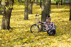 Senior and his bicycle in autumn park. Royalty Free Stock Image