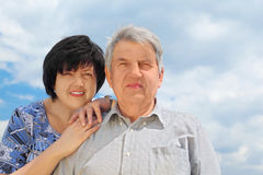 Senior, his daughter leaning to his shoulder. Portrait of old senior, his adult daughter leaning to his shoulder and smiling, sky with clouds, focus on man Stock Photos