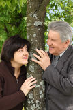 Senior and his daughter standing near tree Stock Image