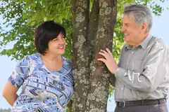 Senior and his daughter standing near tree Stock Photos