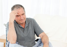 Senior in his wheelchair having a headache royalty free stock images