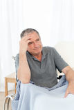 Senior in his wheelchair having a headache Stock Photo