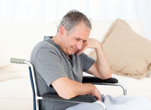 Senior in his wheelchair having a headache Royalty Free Stock Image