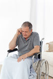 Senior in his wheelchair phoning Royalty Free Stock Photos