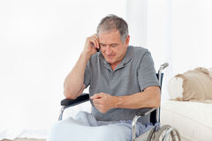 Senior in his wheelchair phoning Stock Image