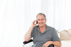 Senior in his wheelchair phoning Royalty Free Stock Images
