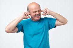 Senior hispanic bald guy plugging ears with fingers hearing loud sounds of music. Senior hispanic bald guy plugging ears with fingers hearing loud sounds of stock photo