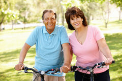 Senior Hispanic couple on bikes. Smiling Royalty Free Stock Images