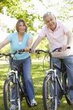 Senior Hispanic Couple Cycling In Park Stock Images