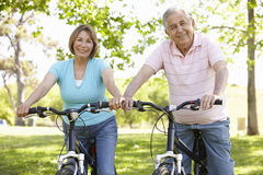 Senior Hispanic Couple Cycling In Park Royalty Free Stock Photos