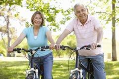 Senior Hispanic Couple Cycling In Park Royalty Free Stock Photos