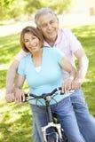 Senior Hispanic Couple Cycling In Park Stock Photos