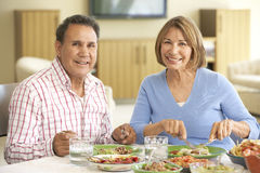 Senior Hispanic Couple Enjoying Meal At Home Stock Images
