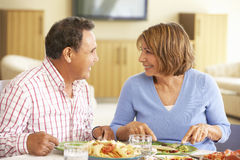 Senior Hispanic Couple Enjoying Meal At Home Stock Image