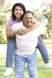Senior Hispanic Couple Having Fun In Park Stock Photo