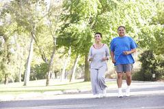 Senior Hispanic Couple Jogging In Park Stock Photos