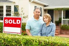 Senior Hispanic couple outside house stock photos