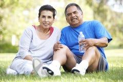 Senior Hispanic Couple Resting After Exercise. Drinking Water Stock Photo