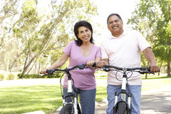 Senior Hispanic Couple Riding Bikes In Park