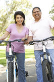 Senior Hispanic Couple Riding Bikes In Park. Smiling Royalty Free Stock Photo