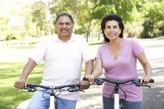 Senior Hispanic Couple Riding Bikes In Park. Smiling Royalty Free Stock Images