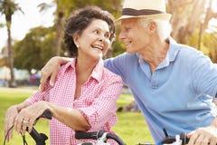 Senior Hispanic Couple Riding Bikes In Park Stock Photos