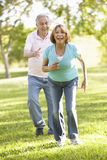 Senior Hispanic Couple Running In Park Stock Photos