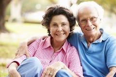 Senior Hispanic Couple Sitting In Park Together Stock Photo