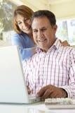 Senior Hispanic Couple Using Laptop In Home Office Stock Photo