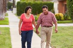 Senior Hispanic Couple Walking Along Sidewalk Together Stock Photo