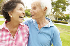 Senior Hispanic Couple Walking In Park Together Stock Photo