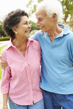 Senior Hispanic Couple Walking In Park Together Stock Image