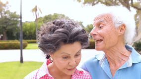 Senior Hispanic Couple Walking Through Park Together. Camera tracks happy senior couple as they walk through park and talk. Shot on Canon 5D MkII at frame rate stock footage