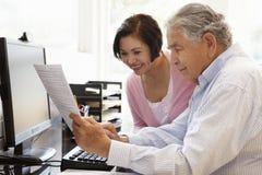 Senior Hispanic couple working on computer at home Stock Photography