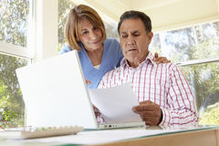 Senior Hispanic Couple Working In Home Office Stock Image