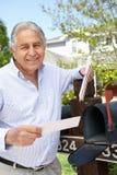 Senior Hispanic Man Checking Mailbox Stock Photo