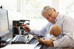 Senior Hispanic man with computer and baby Stock Photography