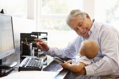 Senior Hispanic man with computer and baby Stock Photography