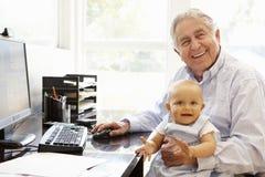 Senior Hispanic man with computer and baby Stock Photo