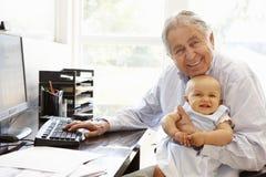 Senior Hispanic man with computer and baby Royalty Free Stock Photo