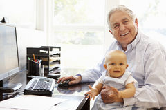 Senior Hispanic man with computer and baby Stock Photos