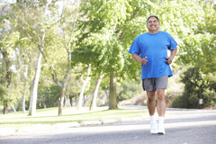 Senior Hispanic Man Jogging In Park Royalty Free Stock Images